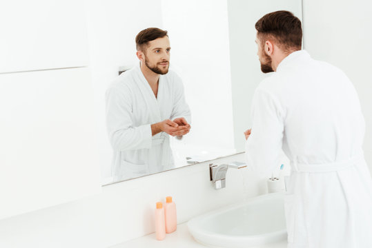 selective focus of handsome bearded man looking at mirror in bathroom