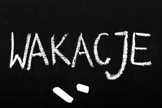 Napis kredą na tabliy szkolnekj: slowo Wakacje