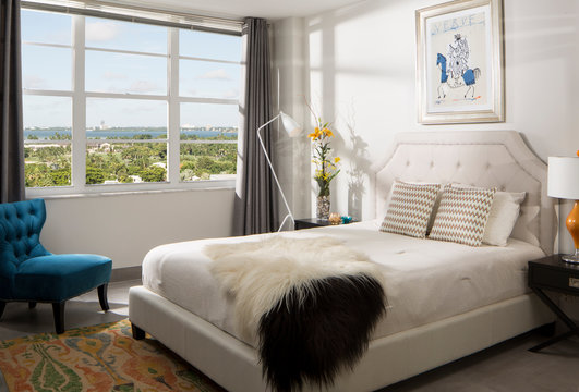 Miami apartment bedroom with view overlooking city with natural afternoon light.