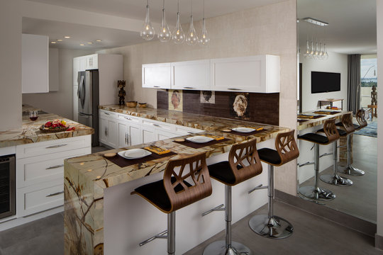 Modern Miami apartment kitchen with wood stools and marble countertops.