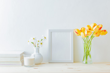 Home interior with decor elements. White frame, yellow tulips in a vase, interior decoration