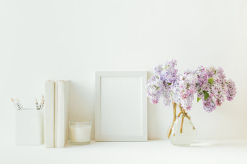 Home interior with decor elements. White frame, branches of lilac in a vase, interior decoration