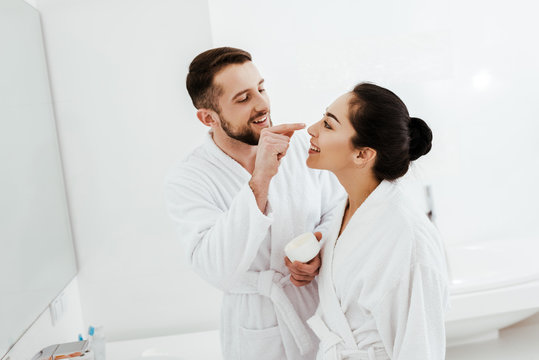 cheerful man applying face cream on nose of attractive girlfriend