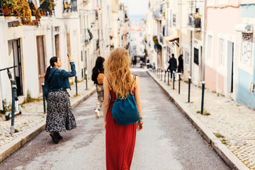 Woman in red dress exploring narrow streets of european city streets