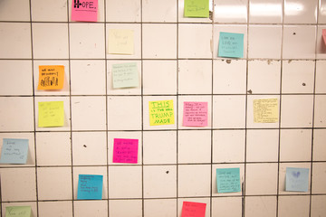 Sticky notes on a tile wall - Medium