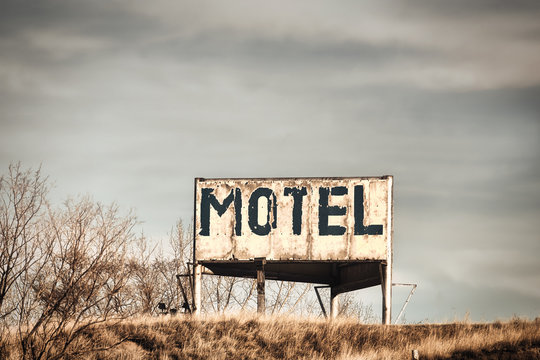 A vintage Motel advertisement on a billboard in a brown grass hill