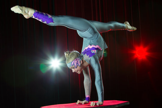 A girl with a flexible body. Performs a circus artist. Circus gymnast. Balancing act. The child performs an acrobatic trick