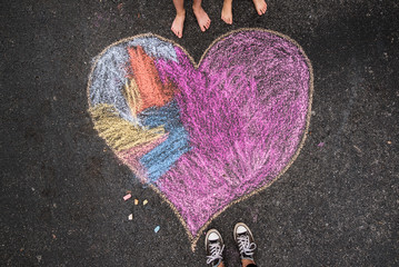 chalk drawing of heart on driveway surrounded by 3 pairs of feet