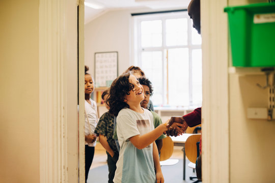 Teacher shaking hand with schoolboy in row at doorway