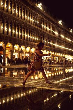 Woman walking outside illuminated St Marks Square at night