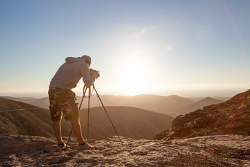 20 30 yrs old photographer taking picture at sunset from a high point