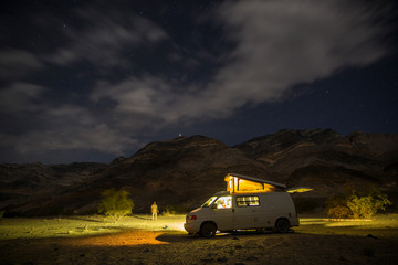 Night image of a man and his camper van in the desert