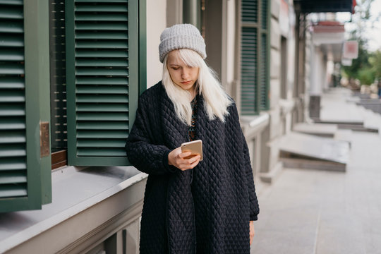 Young beautiful blonde girl standing on the street send message phone