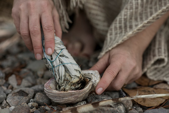 Close up image of woman's hands with a sage smudge stick