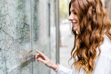 Young businesswoman looking at city map