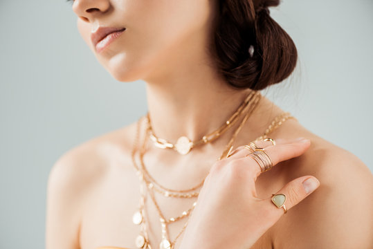 cropped view of young woman with shiny lips in golden necklaces and rings isolated on grey