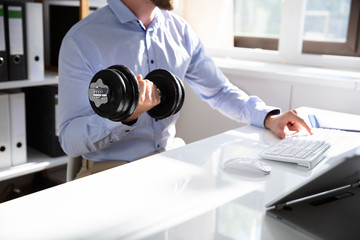 Young Businessman Exercising With Dumbbells In Office