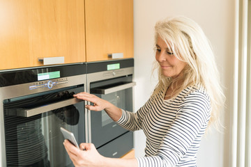 Content mature woman with smartphone checking oven in kitchen of her smart home