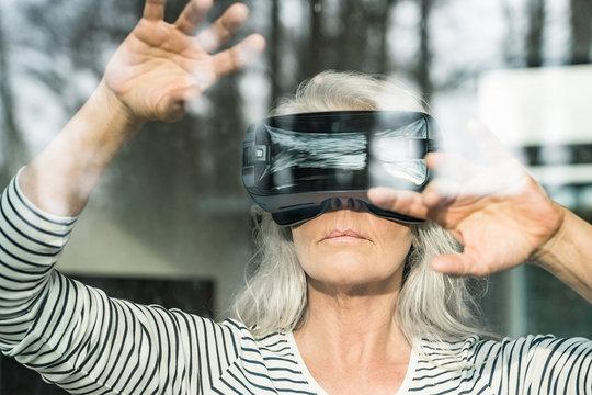 Portrait of mature woman behind windowpane using Virtual Reality Glasses