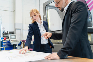 Businessman and businesswoman looking at plan on table in factory