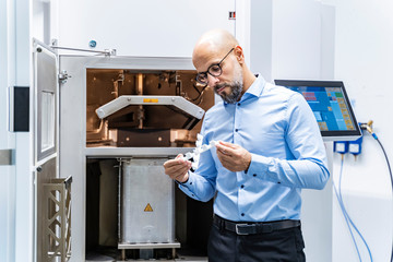 Man holding workpiece at d printer