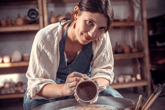 Charming pottery woman works with clay on a potter's wheel. Making pottery.