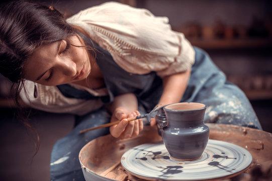 Stylish pottery woman enjoying pottery art and production process. The concept of craft creativity.