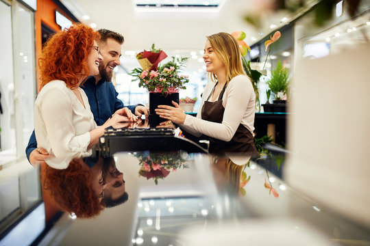 Happy couple and shop assistant with potted plant at counter in flower shop