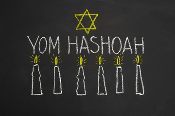 Six candles and inscription on chalkboard Yom HaShoah - Holocaust and Heroism Remembrance Day