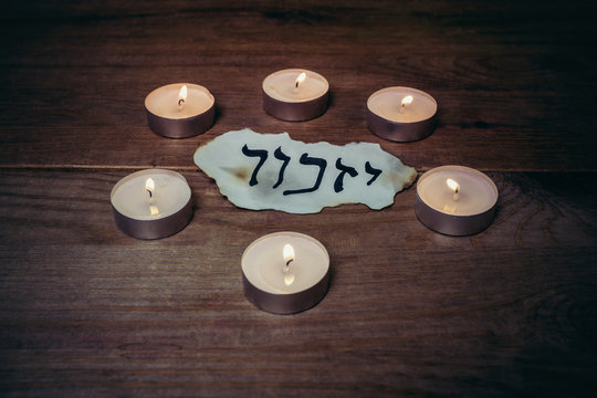 """Hebrew inscription """"remember"""" on a piece of paper and Six candles"""