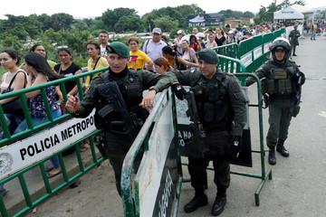 Colombian Police members observe the passage of people on the Simon Bolivar international bridge, after a shooting near to the border between Colombia and Venezuela, in Cucuta