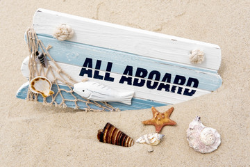 Photoconcept sea travel. Blackboard with the words all aboard, seashells in the sand. Marine photo. Travel, sailor suit