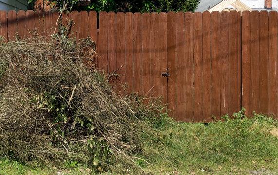 Piled yard cleanup debris against left side of brown wood fence.
