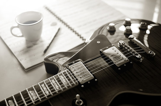 Electric guitar and  a cup of coffee on  background