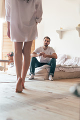 partial view of sexy woman in shirt and bearded man sitting on bed in bedroom