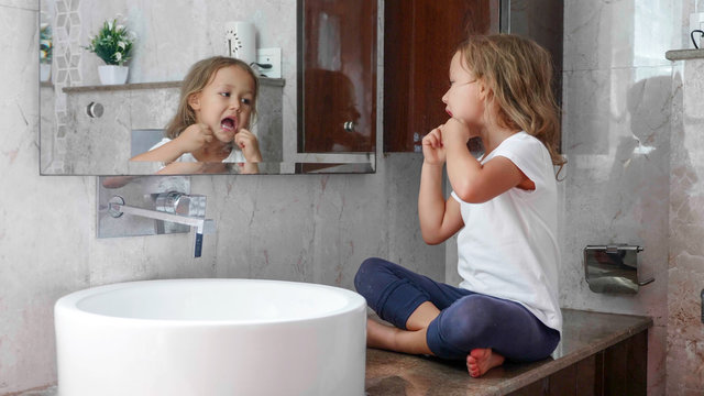Little cute girl brushes her teeth with dental floss while sits on the table near the sink at domestic bathroom in front of the mirror.