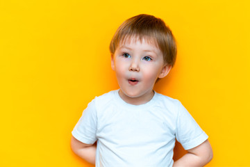 cheerful baby boy three years old in white t-shirt stands on yellow background, open his mouth surprised, blonde hair mixed race asian