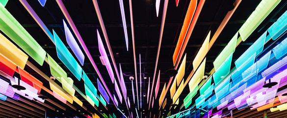 Rainbow colors transparent panels with LED lights that decorated with ceiling. Perspective background.