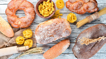 Gluten free food. Various pasta, bread, snacks and flour on a white wooden background. Top view. Free space for your text. Wall mural