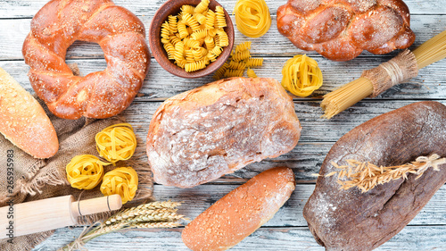 Wall mural Gluten free food. Various pasta, bread, snacks and flour on a white wooden background. Top view. Free space for your text.