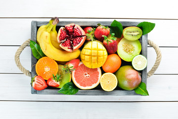 Fruits in a wooden box. Citrus, melon, pomegranate, strawberry, banana. Top view. Free space for your text. Wall mural