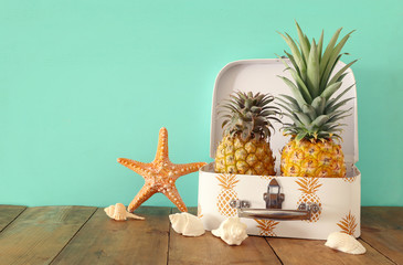 Autocollant pour porte Plage Ripe couple pineapple in suitcase over wooden table or deck. Tropical summer vacation concept