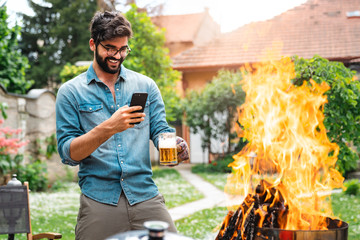 Handsome young male taking pictures with mobile phone of barbecue in back yard