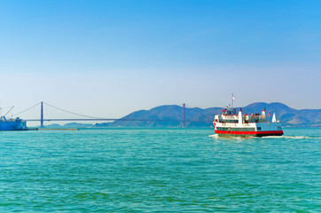 View of a ferry running on San Francisco Bay with Golden Gate Bridge in the background in San Francisco.
