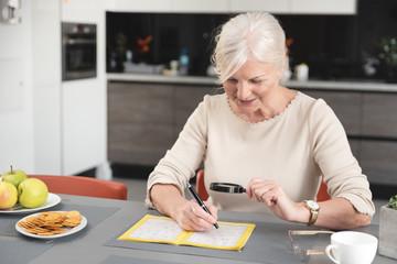 Senior woman enjoys solving a crossword puzzle Wall mural