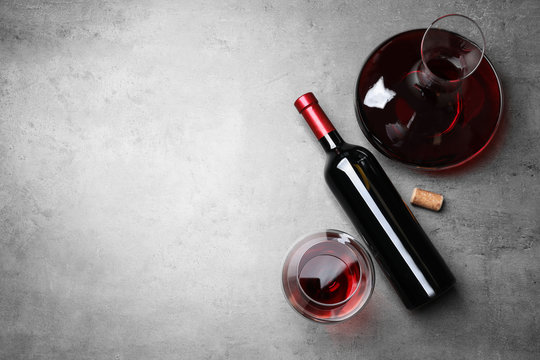 Decanter, glass and bottle with red wine on color background, flat lay. Space for text