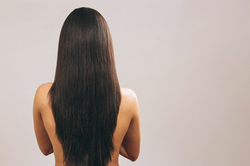 Young woman with long black hair posing on camera. Showing lenght of it. Smooth treasure. Standing back to camera. Naked. Isolated on light background.