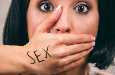 Young scared woman with black hair posing on camera. Hand on mouth. Written work sex. Concept harassment. Cutview. Isolated on light background.