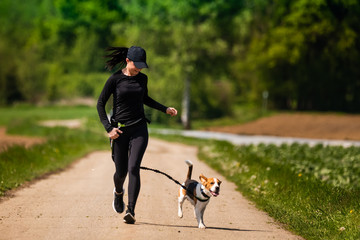 Sport girl is running with a dog (Beagle) on the rural road towadrds camera.