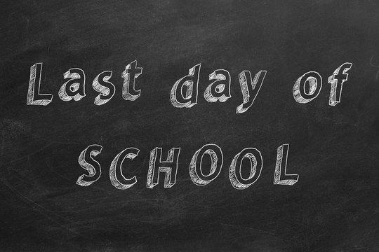 "Hand drawing text ""Last day of SCHOOL"" on blackboard."